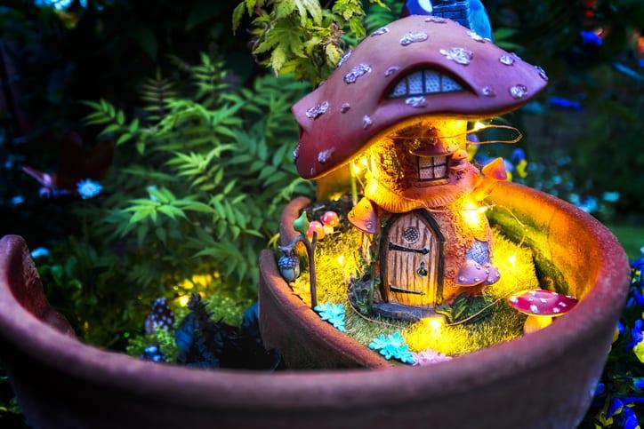 Lighted fairy house in broken garden pot at night