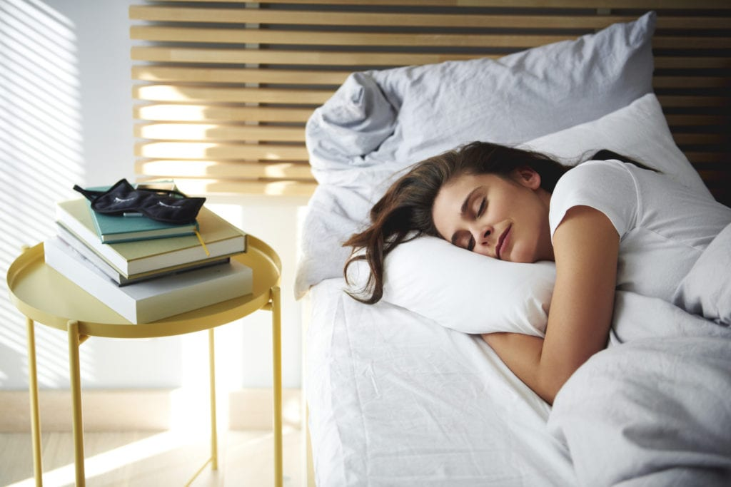 Young woman napping on new mattress