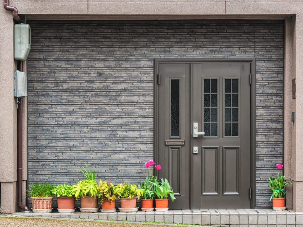 Gray front door with small square decorative windows and flower pots in front of it