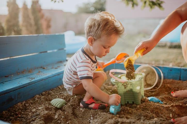 Child plays in his backyard sandbox