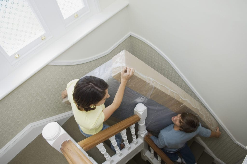 A couple moves their mattress into their new home