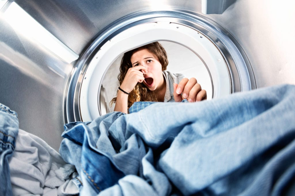 Laundry left in dryer stinks! Unhappy woman holds nose.