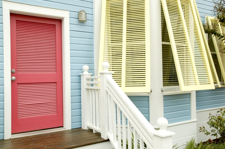Yellow shutters, a coral door and blue wood siding