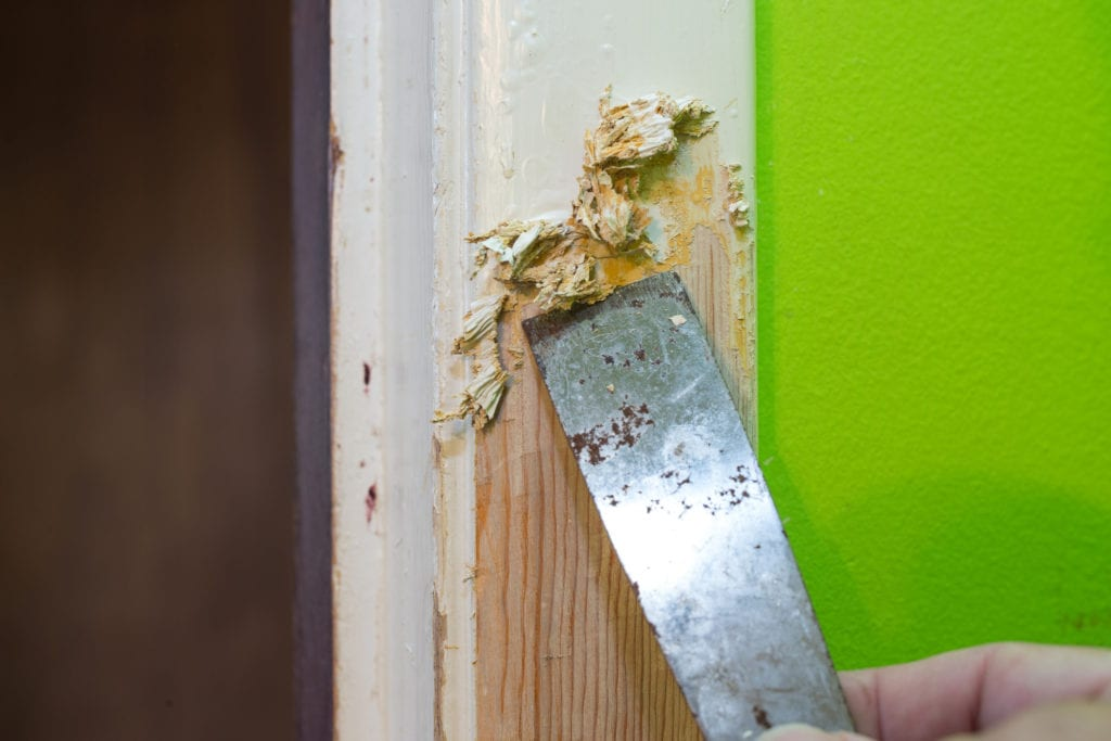 Layers of paint are removed from wood.