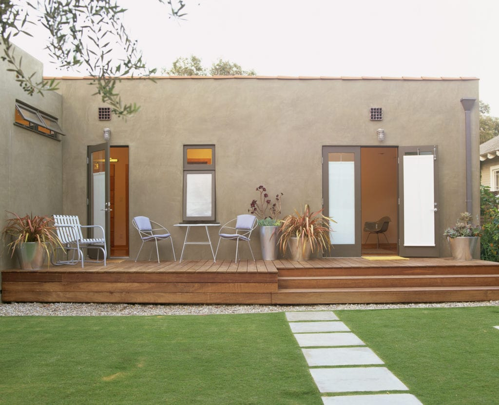 Concrete path leads to modern home in backyard