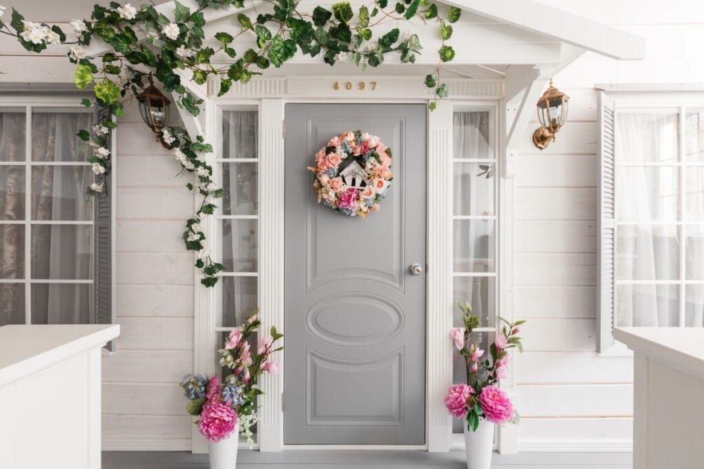 Entrance of home with light gray door, wreath, and spring flowers