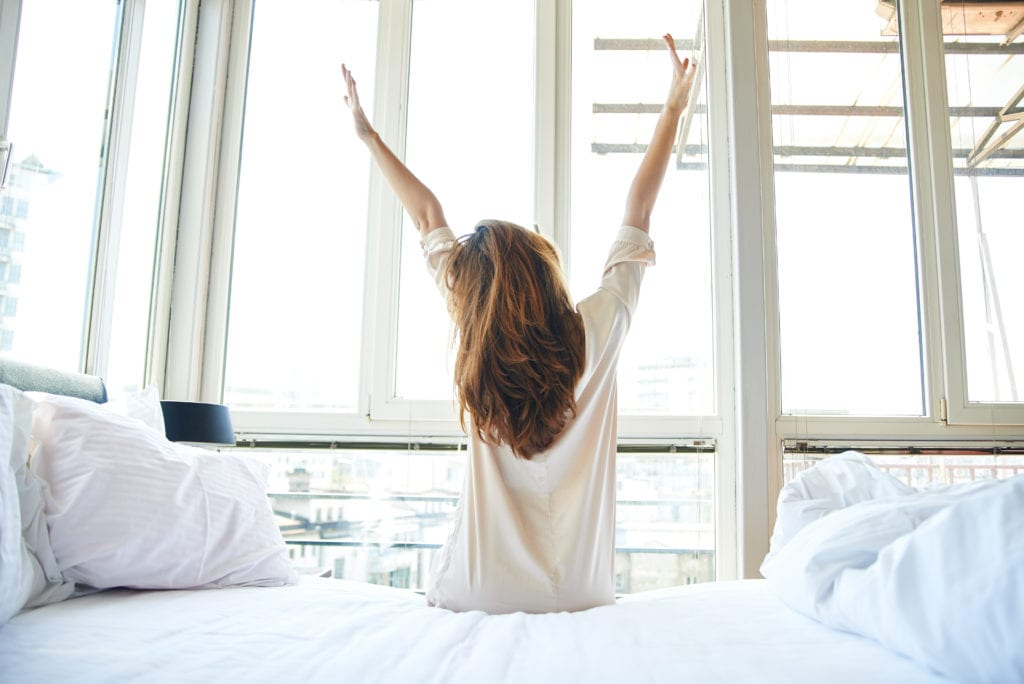 Woman waking up and stretching in the morning