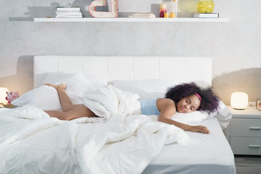 Woman sleeping comfortably on her bed