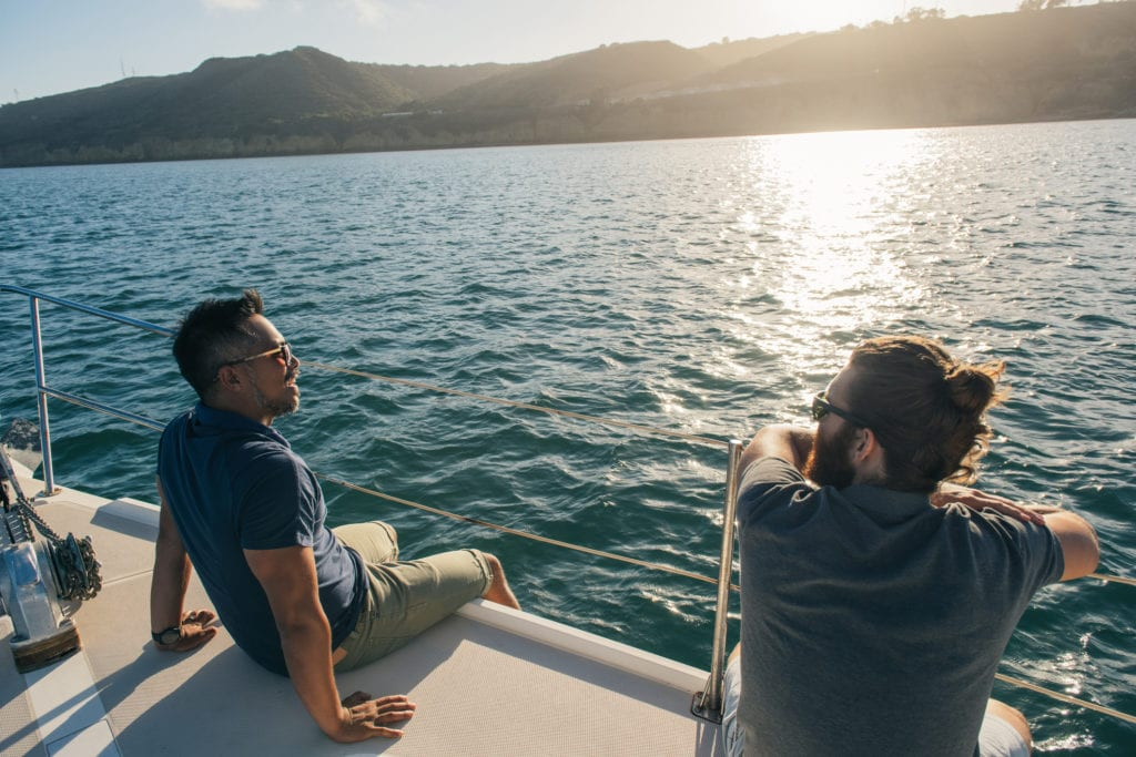 Friends enjoying view on sailboat, San Diego Bay, California, USA