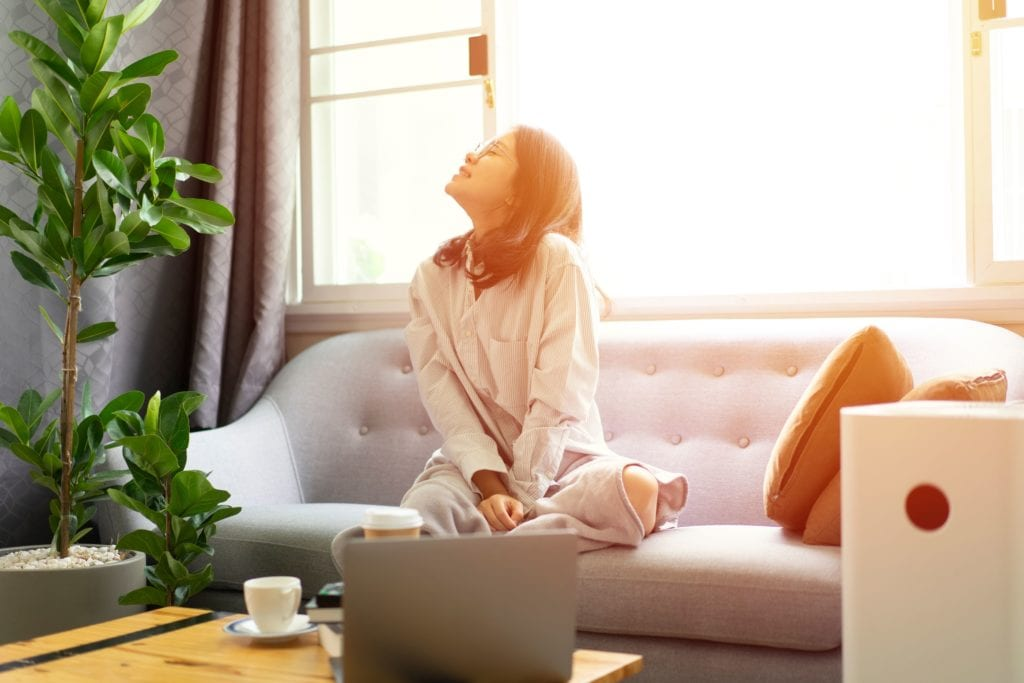 woman feeling fresh and happy, sitting on sofa with laptop computer and air purifier
