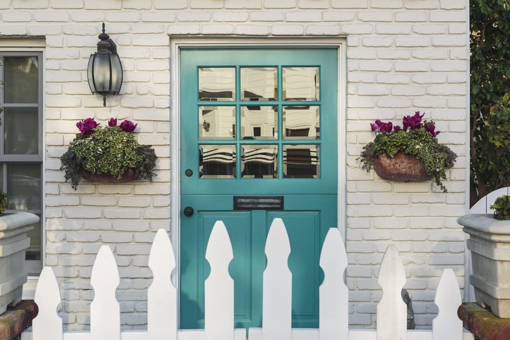A teal wooden front door to a home, with white picket fence gate in foreground. The door is framed by two flower planters, and detail of the white, brick house.