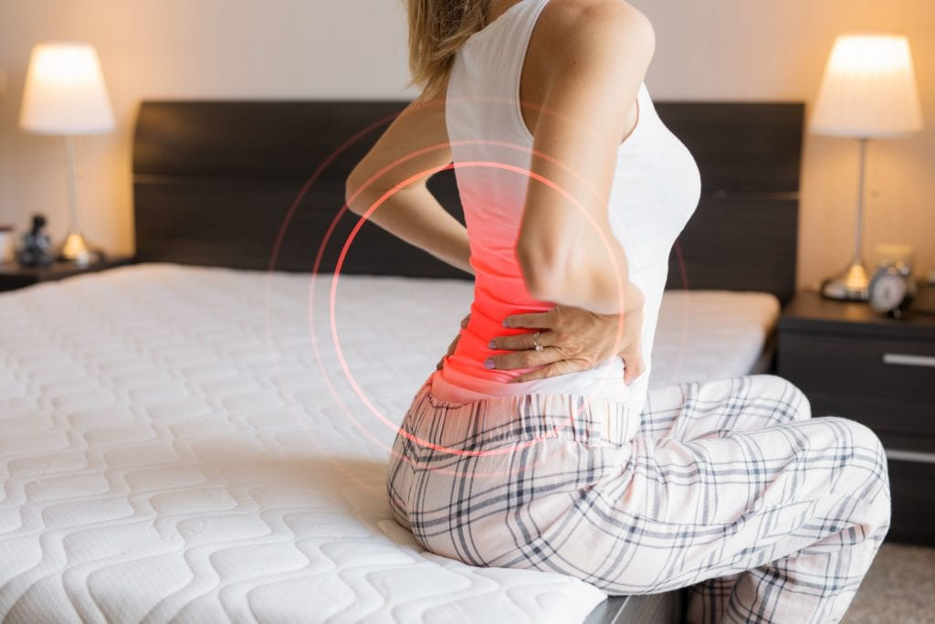Woman with back pain sitting on mattress