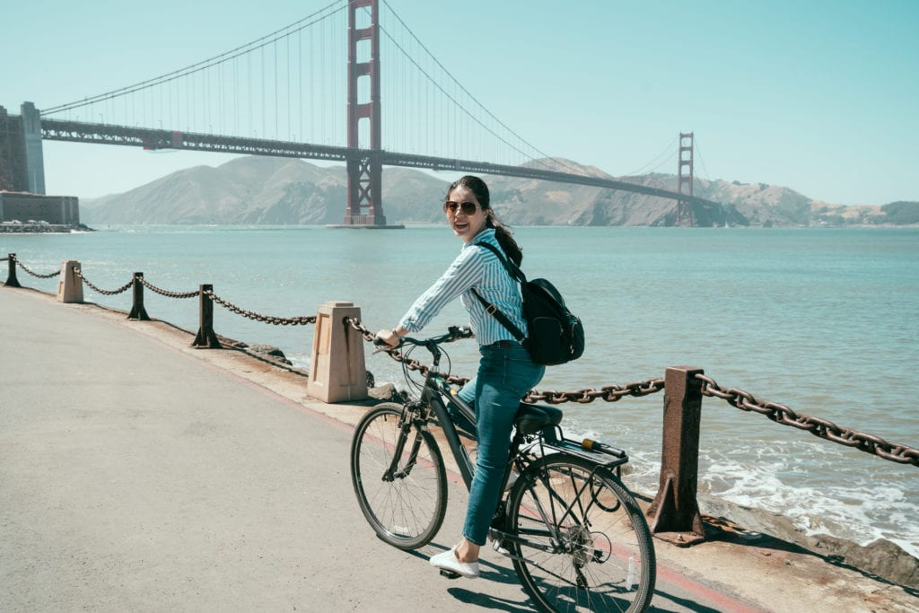 Woman biking in San Francisco in front of Golden Gate Bridge