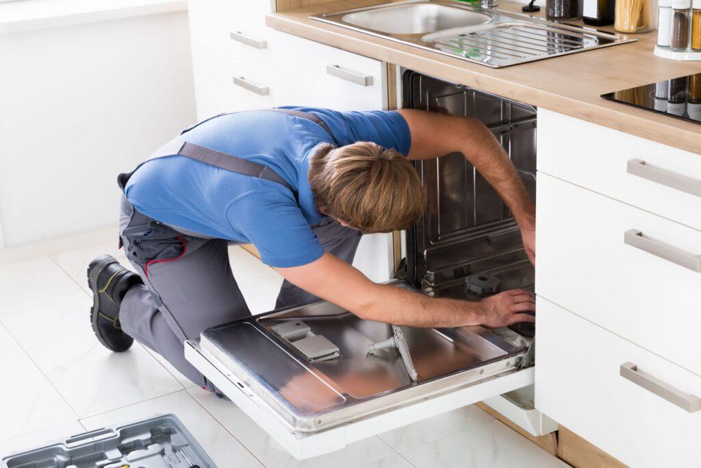 Repairman fixing a dishwasher in minimalist kitchen