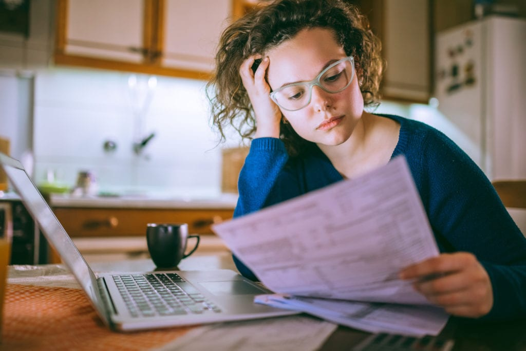 Young brunette curly female reading her rent lease, looking stressed