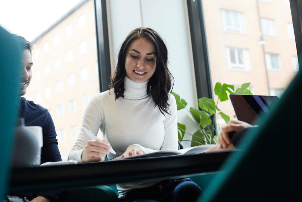 Smiling woman with man signing property papers at real estate office