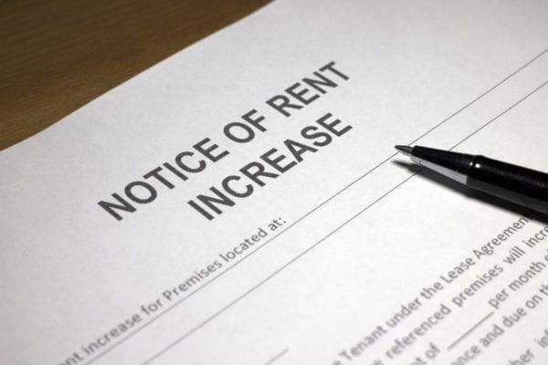 Someone filling out Notice of Rent Increase.