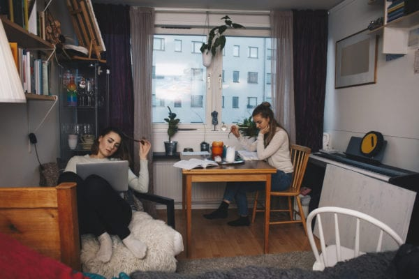 Girls studying in a room with curtains in the window