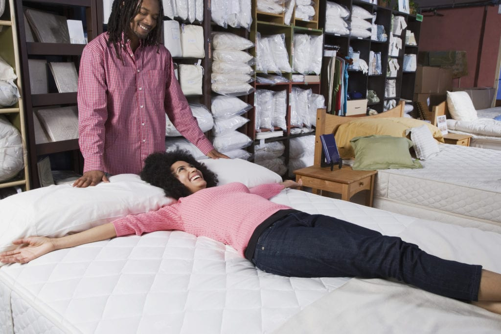 Young couple tests out a mattress at a store.