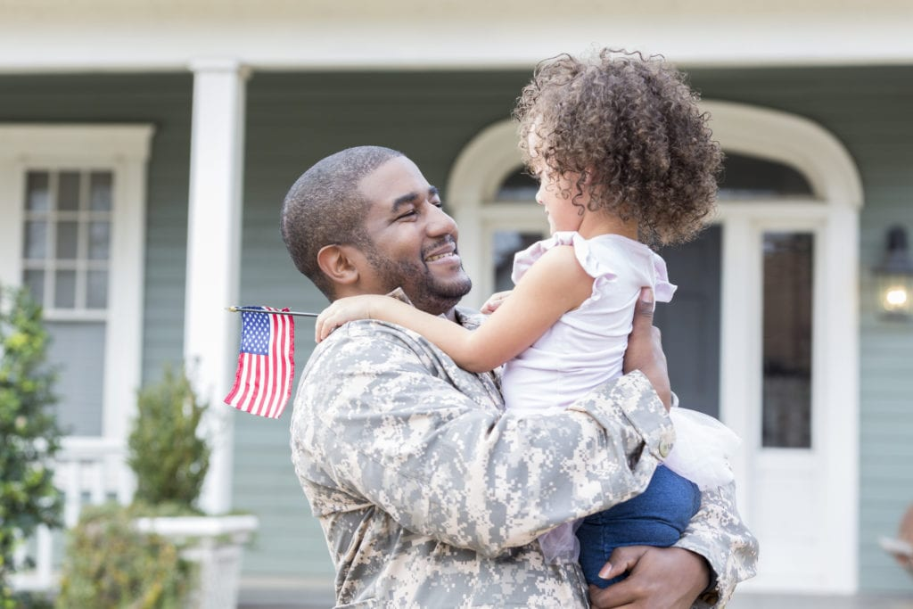 Happy mid-adult soldier picks up his preschool age daughter as he returns home from assignment.