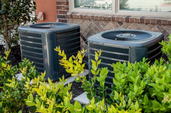 Heating and air conditioning units on the side of a brick building, hidden by shrubs