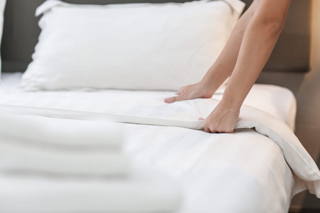 Hands Making Bed with white comforter and pillow