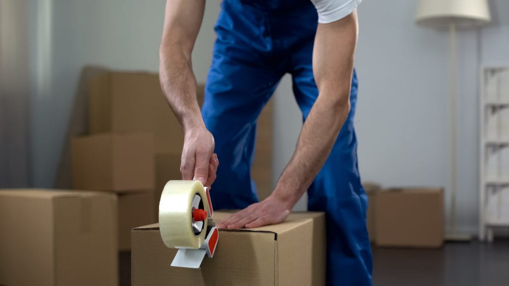 Moving company worker packing cardboard boxes