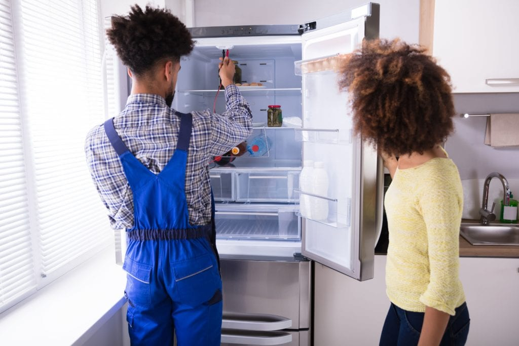 Woman Looking At Male Repairman Checking Refrigerator With Digital Multimeter