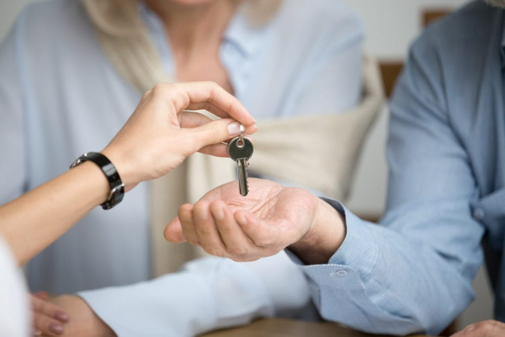 Couple of renters getting key to new apartment from landlord