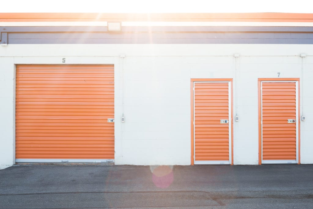 Sun overhead storage units with white walls and orange doors
