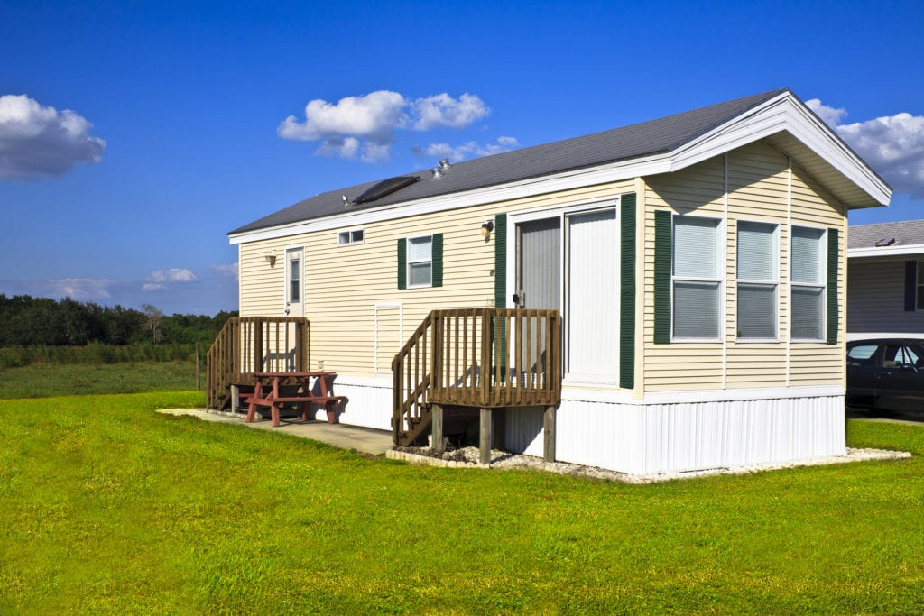 Mobile home located in a trailer park with extensive front yard. Also called a manufactured home, holiday home and static caravan. (Mobile home located in a trailer park with extensive front yard. Also called a manufactured home, holiday home and st