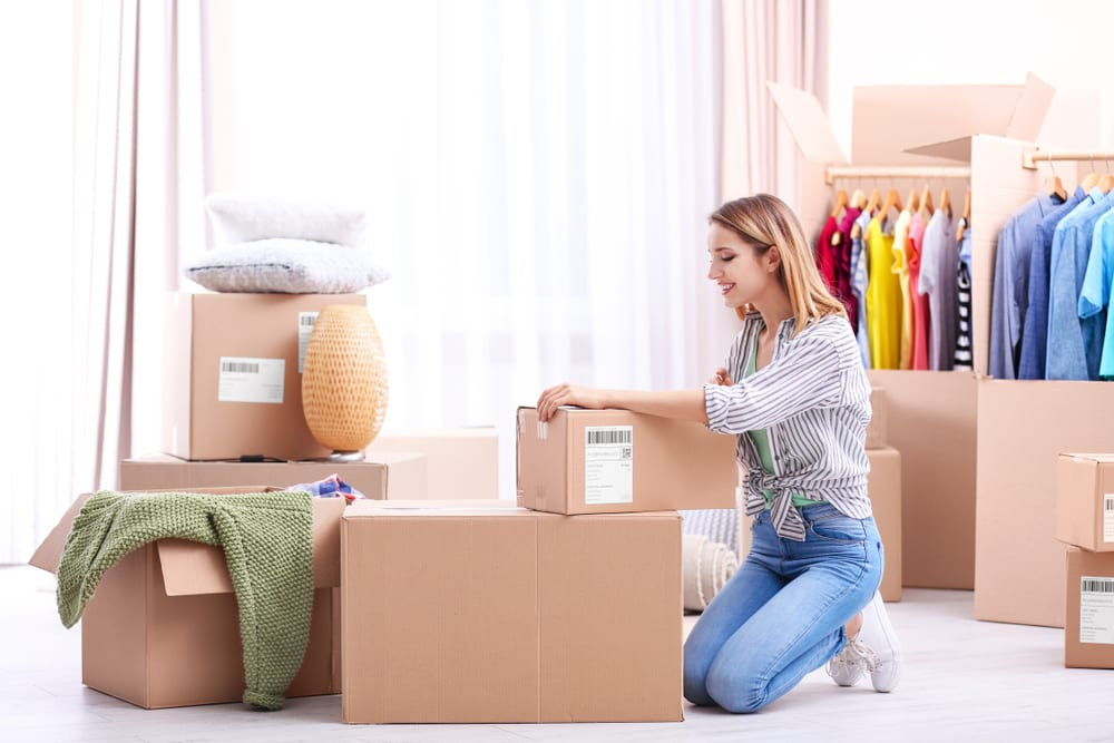 A young woman packs her closet for her upcoming move