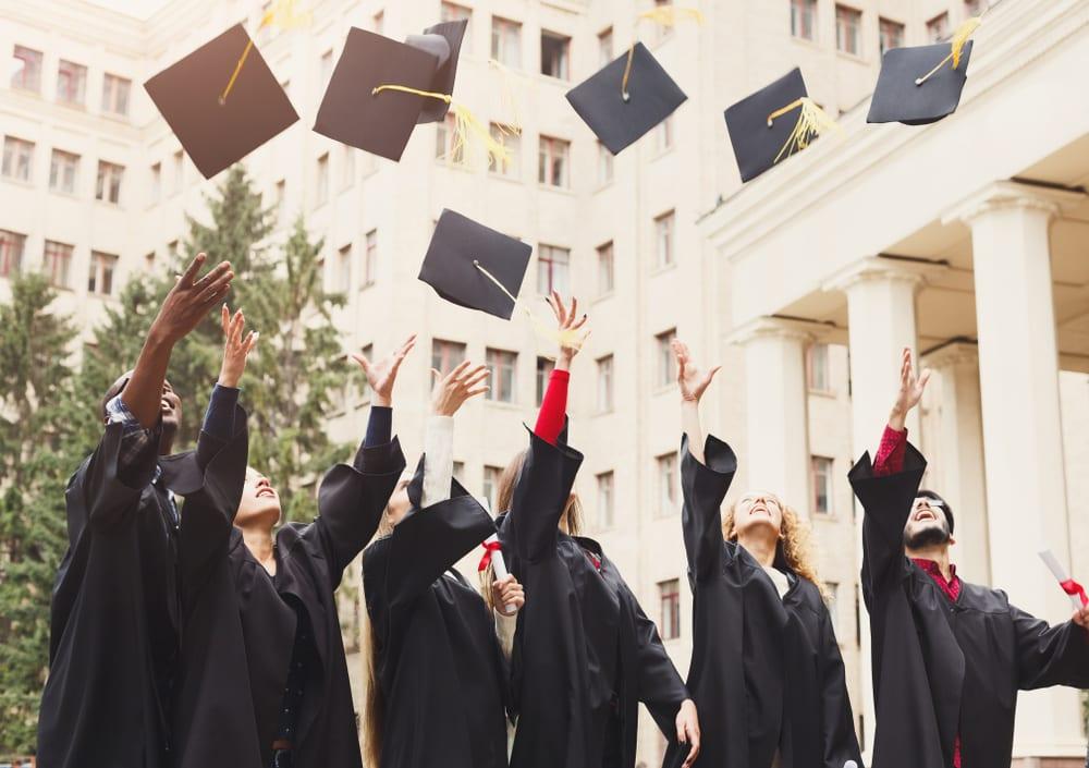 Graduates throw their caps into the air