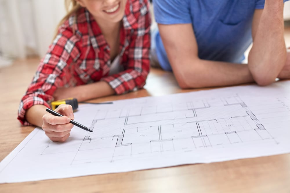 Husband and wife look over blueprints for an upcoming remodel