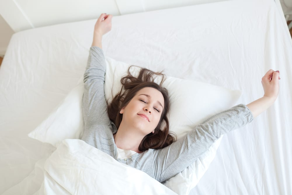 Woman wakes up and stretches on her Leesa mattress
