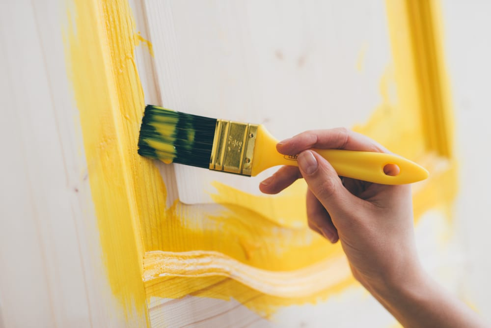 A close-up of a woman's hand painting a door yellow
