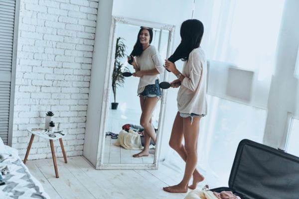 Girl looking in full-length mirror