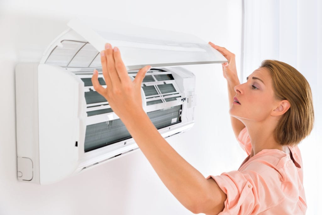 Woman opening wall AC unit to repair it