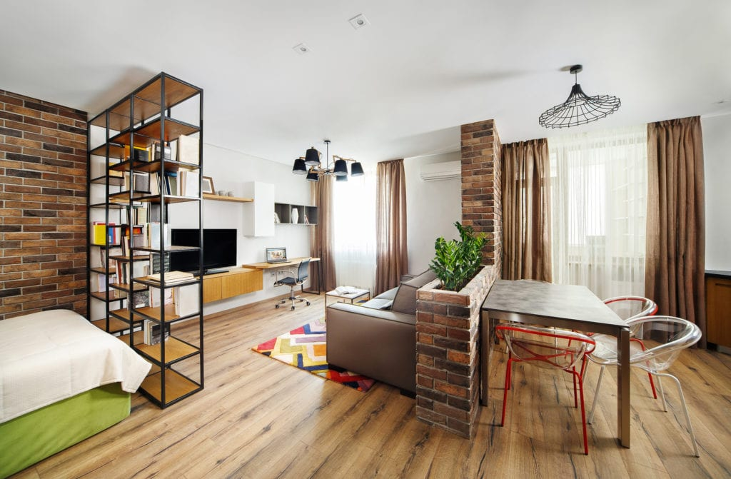 Interior studio apartments, with bookshelves and hardwood floors.