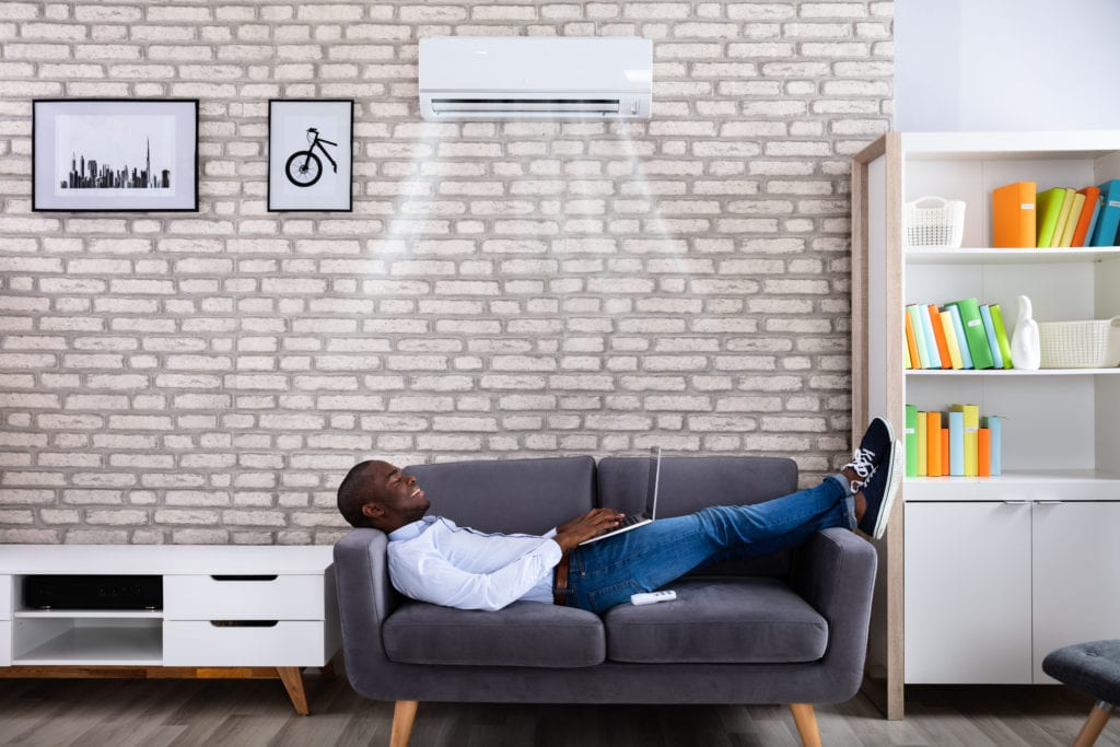 Man on couch enjoying ductless cooling unit