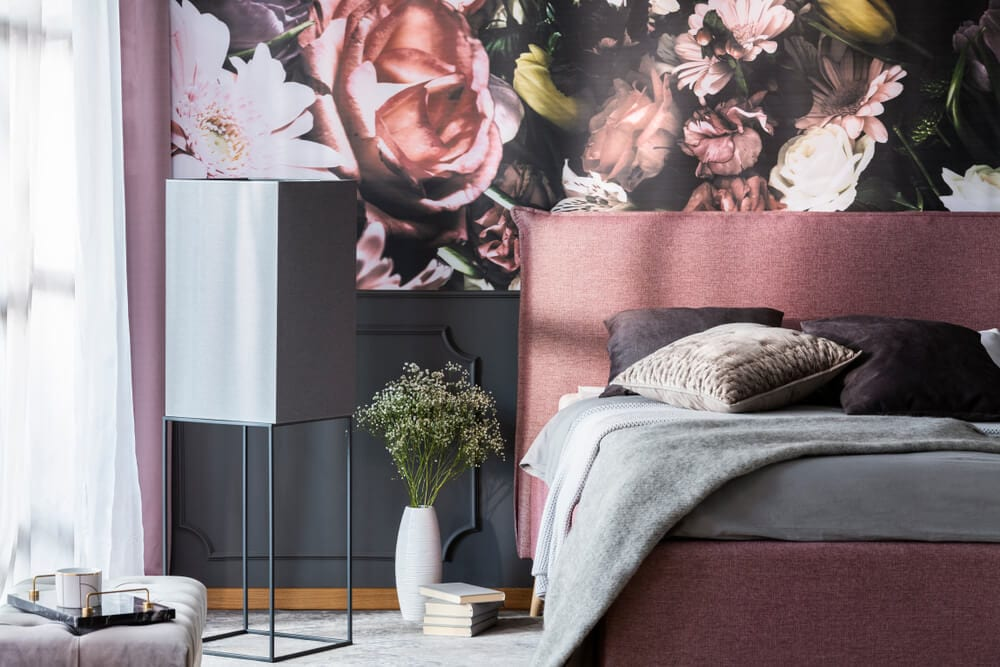 Modern bedroom with pink bed and floral wallpaper accent wall