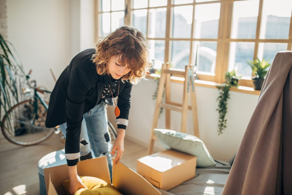 Young woman moving in into college apartment