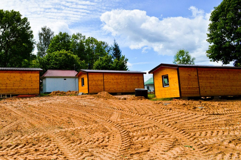 Three prefabricated or modular homes are being finished on dirt construction site