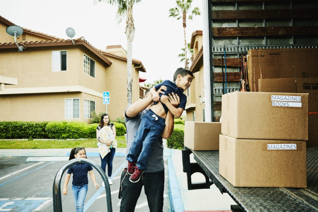 Father lifting smiling son into back of moving truck