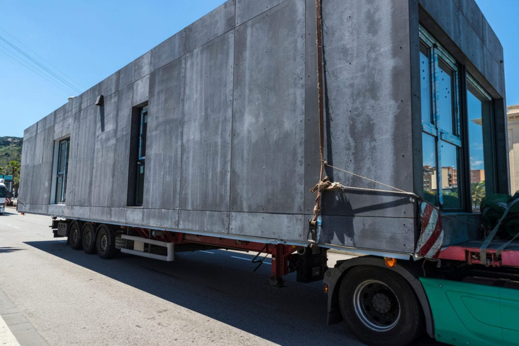 A modular home is being transported on a truck