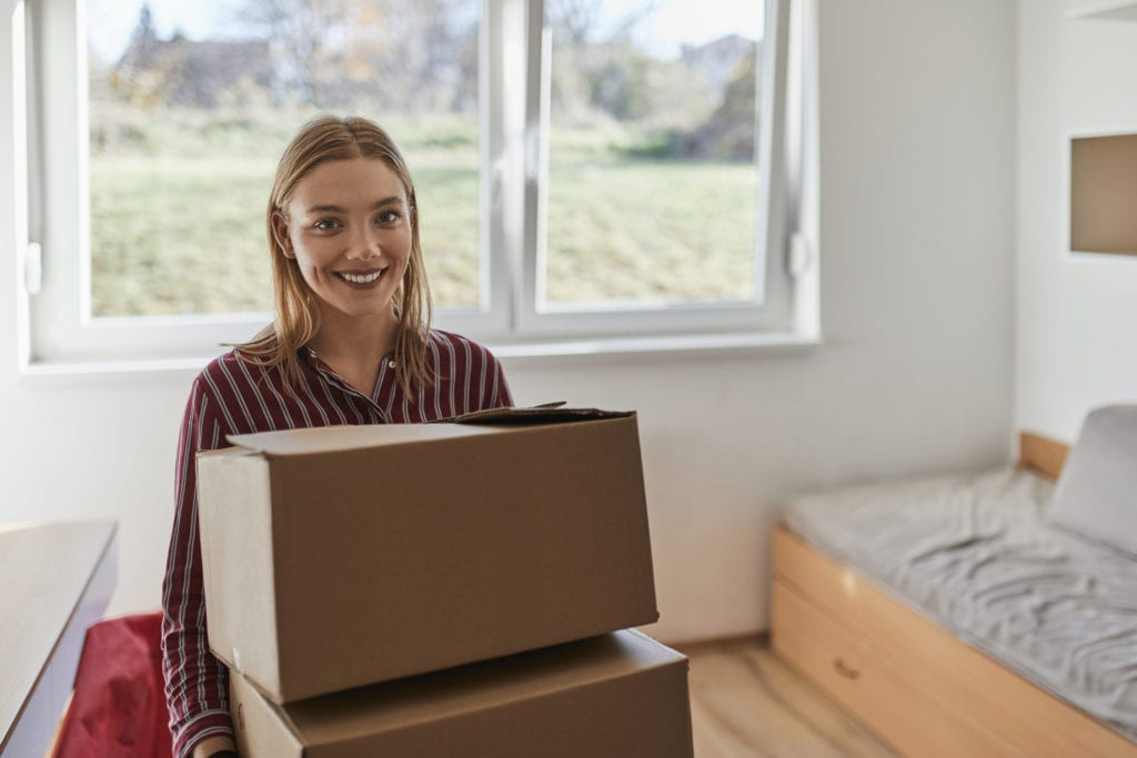 Young woman moving into college dorm