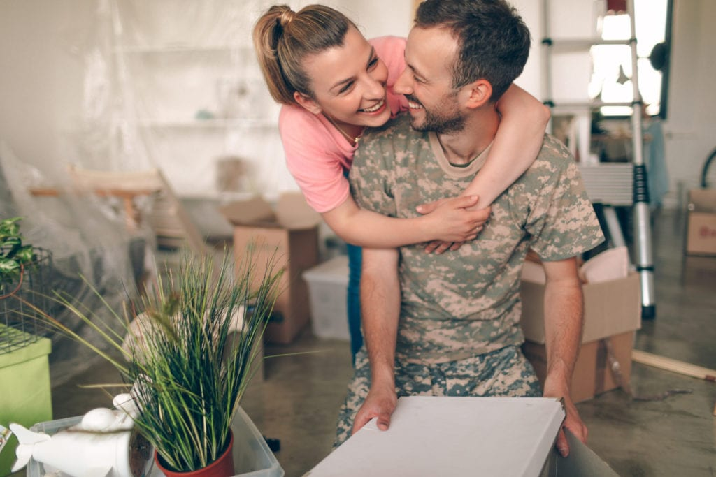 Photo of a young man in a soldier uniform, moving into a new apartment with his wife