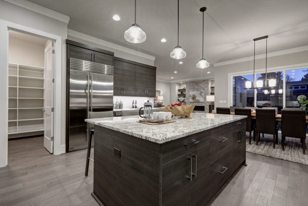Modern kitchen with dark gray cabinets and open door to pantry