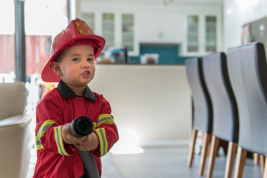little boy in firefighter uniform wields a fire hose