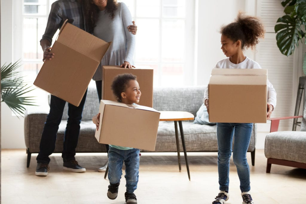 Family with kids holding boxes and moving into new home